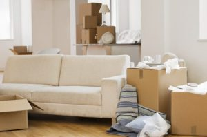A living room with sofa surrounded by cardboard boxes as if someone is moving in 7 days.