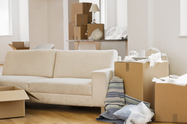 A living room with sofa surrounded by cardboard boxes as if someone is moving in.
