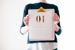 woman holds a calendar - start your search on time