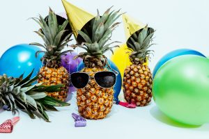 Three pineapples wearing party hats, and one wearing sunglasses, surrounded by colorful balloons and party items. This is something that you can expect after moving to Florida.