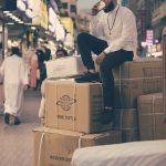 Man sitting on some boxes.