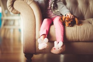 Girl and dog sitting on a couch.