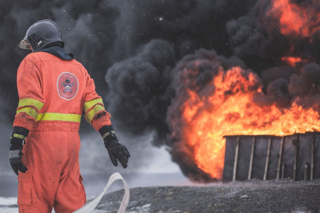 A firefighter in his gear, with fire and smoke in the background.