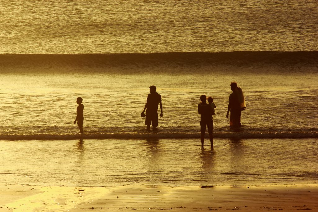 A family of five, knee-deep in water at the beach.