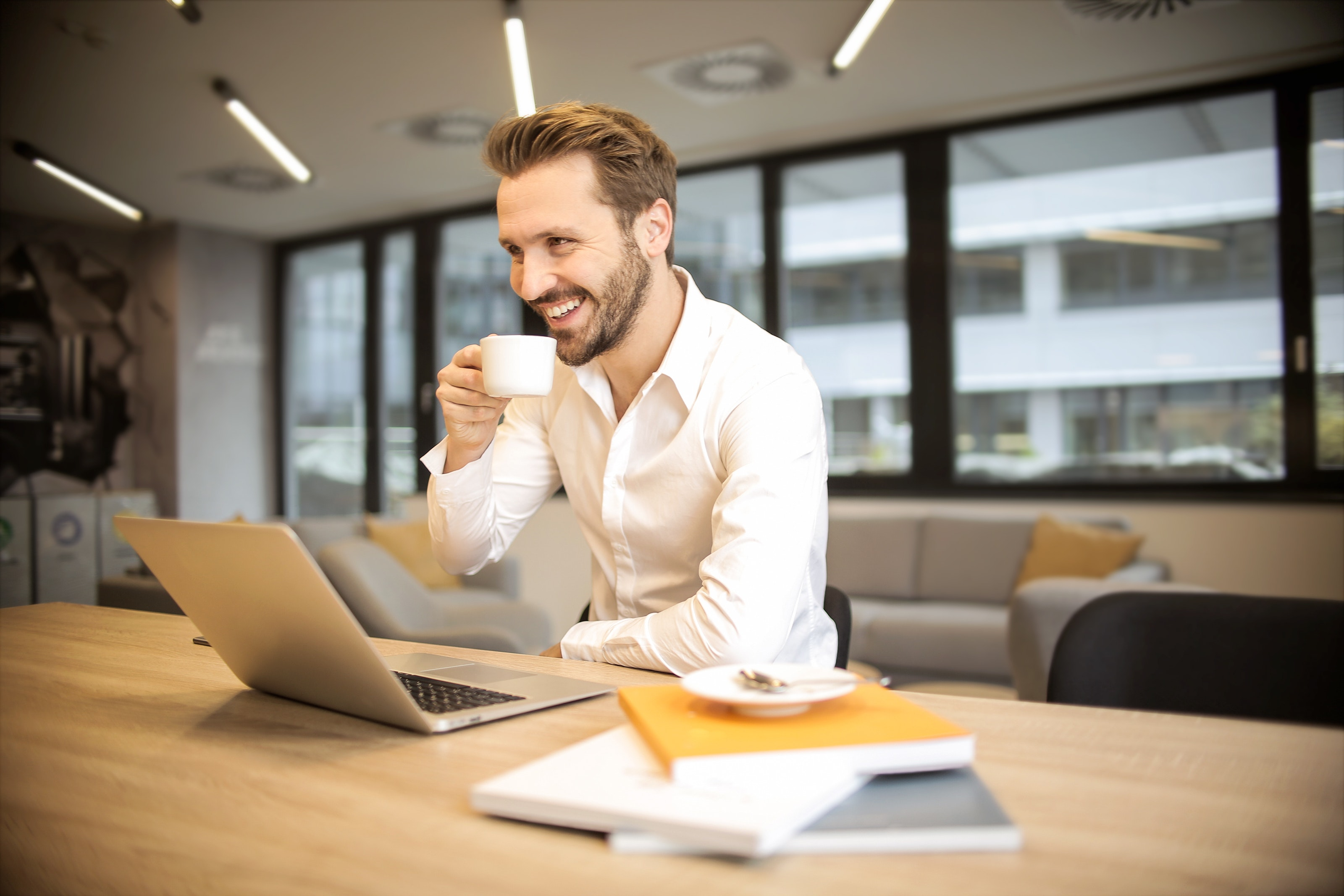 A man smiling and drinking coffee as he works on a laptop.