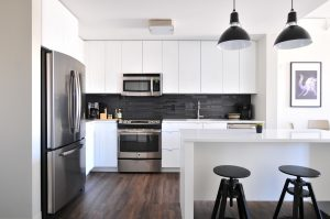 A clean kitchen, with black and white furniture, appliances and details.