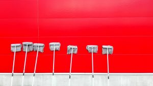 Seven white brooms arranged against a red wall.