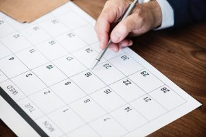 A man pointing at a calendar with a pen, as one of unpacking tips