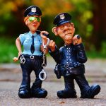 Two small figurines of police officers with batons and handcuffs.