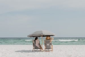 Two people relaxing on a beach during the day.