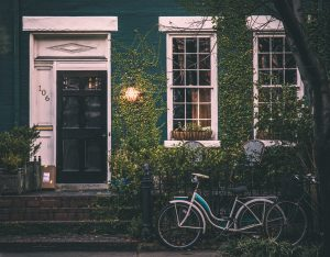 A house with two bikes in front and vine growing up the walls.
