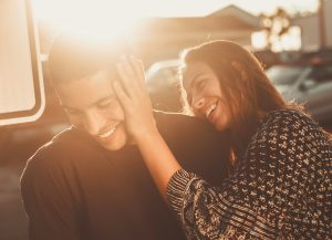 A couple smiling at sundown.