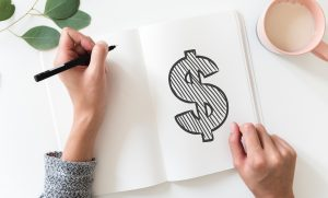 A woman sketching a giant dollar sign across a notebook page. - Saving money is one of many reasons to hire professional movers.