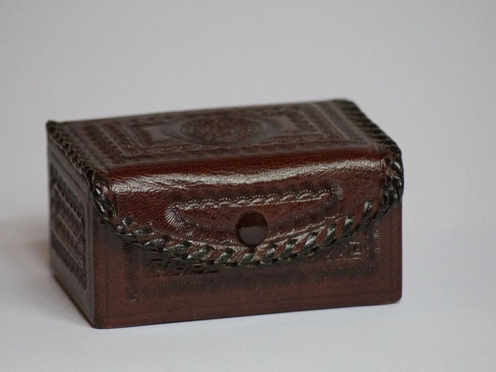 A small wooden chest on a white surface.