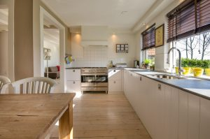 The interior of a clean, white kitchen with wooden floors.
