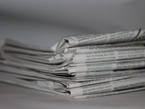 A stack of old newspapers, which will be used to safely pack fragile items.