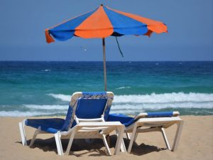 A beach with two deck chairs and an umbrella, where you will relax after Key Largo movers are done.