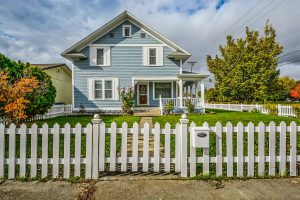 A light blue house with a white picket fence and a cut lawn, as an example for when you estimate property value.