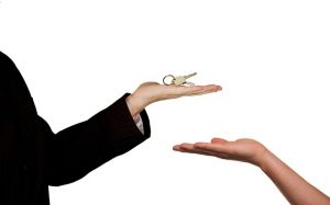 Someone giving keys to a home buyer.