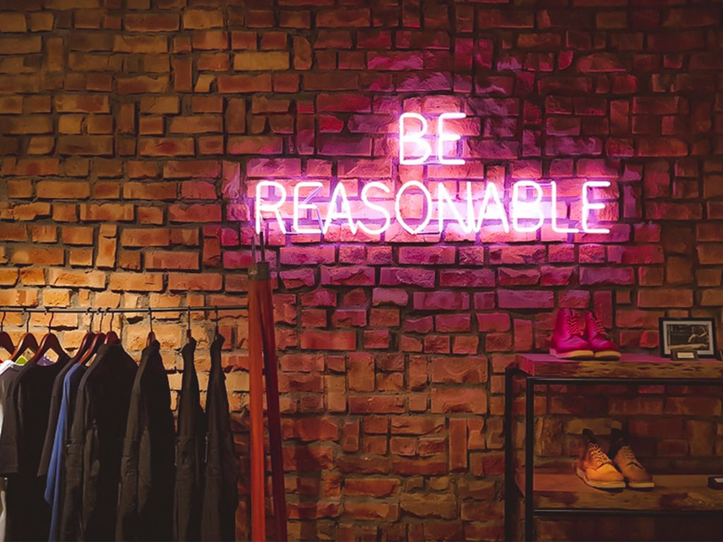 A wall with a purple neon sign saying 'Be reasonable'.