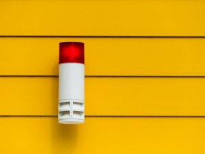 A white home alarm on a yellow wall.