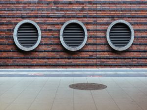 A row of three round vents on a building wall.