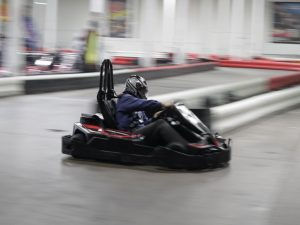 A person in a go-kart making a turn on the track.