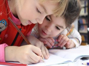 Two small girls writing in a notebook. - Parkland is great for families and that is why families move to Parkland in the first place.