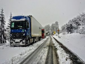 A snowed in truck moving across an icy road.