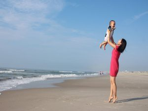 A mother in a pink dress playing with her infant son on a beach, as one of the reasons why families move to Fort Lauderdale.