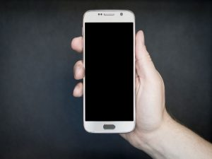 A person holding a locked smartphone.