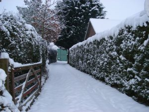 A driveway to a house, covered in snow.