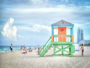 A beach in Florida during the day, with a lifeguard's post and people enjoying themselves.