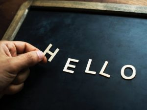 A person spelling 'hello' with letters on a blackboard, representing a call to movers Sunrise FL.