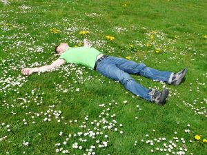 A man laying relaxed in a field.