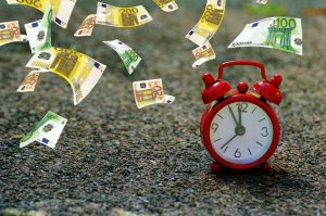 A red alarm clock and euros falling on the ground.