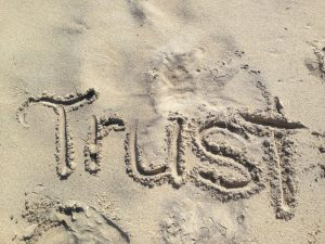 The word 'Trust' written in the sand.