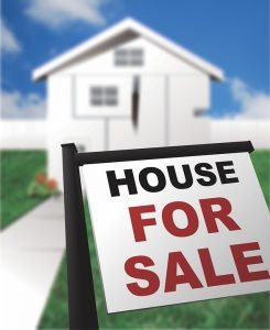 A house for sale sign in front of a property.