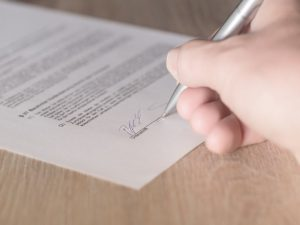 A person signing a legal document.