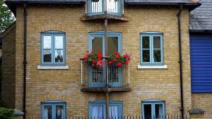 A balcony with red flowers.