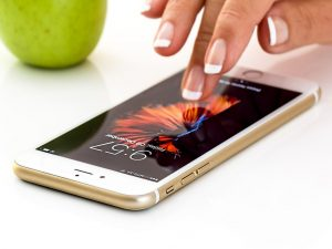 A woman unlocking a smartphone, that's next to an apple on a white surface.