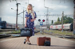 Girl with a suitcase at the train station.