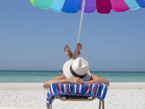 A person with a hat relaxing on a beach.