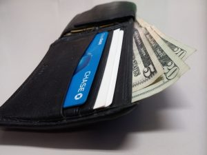 A wallet with cards and dollar bills, on a white surface.