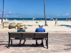 Two elderly people sitting on a bench by the beach.