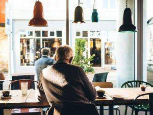 An elderly man sitting in a cafe after retiring in miramar.
