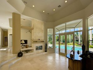 A spacious home interior with a swimming pool visible in the yard.