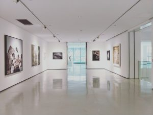 an inside of a museum, with paintings on the white wall