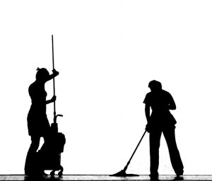 Two individuals cleaning floor with the mop