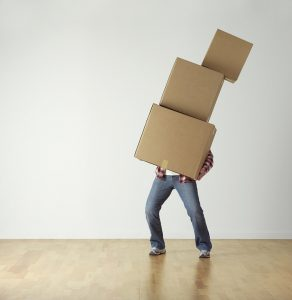 a man carrying three boxes in his arms in an empty room